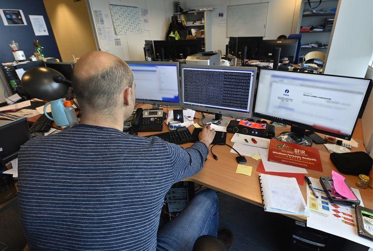 Een agent van de Federale Computer Crime Unit in Brussel. Beeld Belga