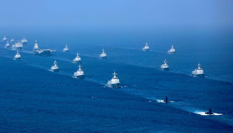 Het vliegdekschip Liaoning tussen andere marineschepen tijdens een oefening in de Zuid-Chinese Zee in april.  Beeld AP