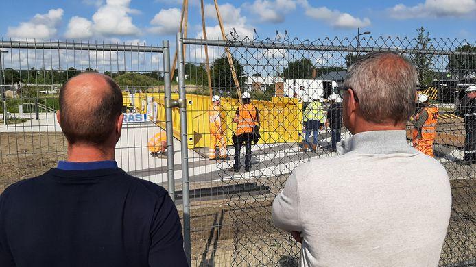 De brug over de Roosendaalse Vliet in de nieuwbouwwijk Stadsoevers ligt op zijn plek. Wethouder Toine Theunis (re) en projectleider Stadsoever Gerben van Dijk kijken toe.