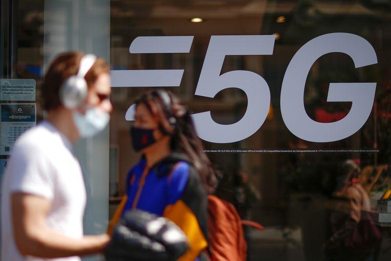 Mensen langs een 5G-advertentie in een winkelruit.  Beeld REUTERS