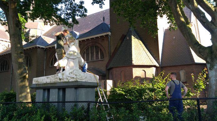 Koen (links) en Thomas (rechts)  terwijl ze in Zundert het Heilig Hartbeeld (met geknielde religieuze) schoonmaken