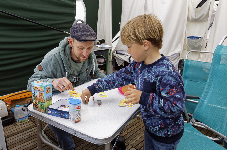 Vader Jelle en zoon Tygo spelen een spelletje bij de kachel.