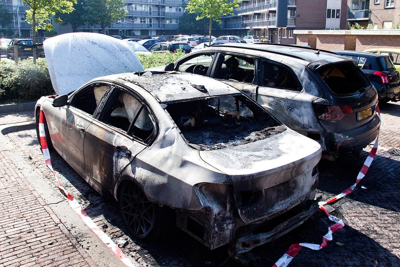 Het recentste doelwit was een witte BMW (grote foto). Bij twaalf andere plekken verdeeld over heel de stad werden nog eens 23 auto's in brand gestoken.