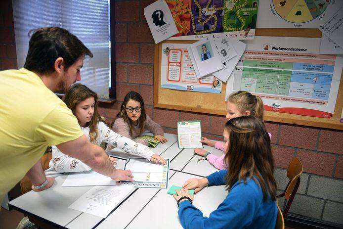 Het zesde leerjaar van VBS De Plein speelt in groepjes een geldwegspel.