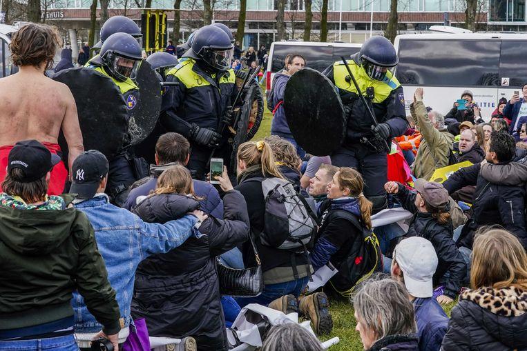 Een deel van de demonstranten werd door de ME en de politie te paard verdreven, een ander deel ging zitten op het gras. Ze werden beschoten met het waterkanon.  Beeld ANP