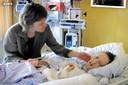 Moeder Maybritt aan het bed van haar dochter Carina.
