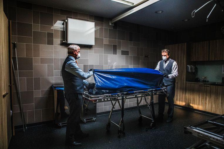 Uitvaartverzorgers van het Dela-uitvaartcentrum in Den Bosch, waar een witte mobiele koeling ter grootte van een zeecontainer extra ruimte voor lichamen moest bieden. De pijnlijke realiteit van oversterfte werd op weinig andere plekken zo tastbaar.   Beeld Aurélie Geurts