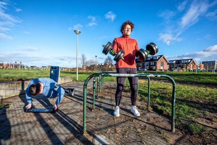 Twee jongens zijn op Eerste Kerstdag aan het fitnessen op een veld in de wijk Tuinlanden, Utrecht.  Beeld Raymond Rutting