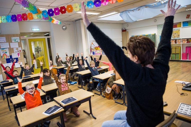 Kinderen van groep drie van de Katholieke basisschool Willibrordus te Oud-Beijerland  laten maandag aan juf Angela Nienhuis zien hoe blij ze zijn dat de school weer open is. Beeld Arie Kievit