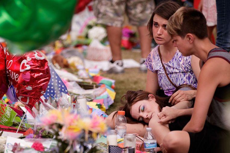 Rouwenden bij de plaats in Orlando waar bloemen worden gelegd voor de slachtoffers van het bloedbad. Beeld afp