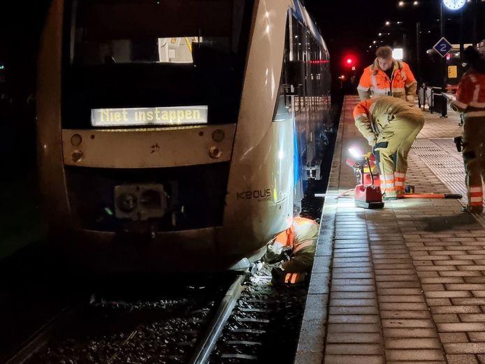Medewerkers van ProRail proberen het verkeersbord onder de trein vandaan te halen.