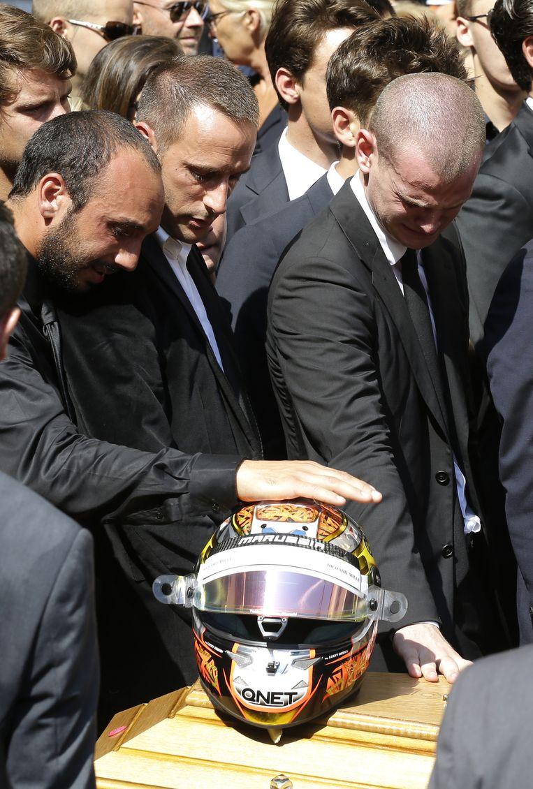 Vrienden raken de helm aan op de kist van Jules Bianchi. Beeld AP