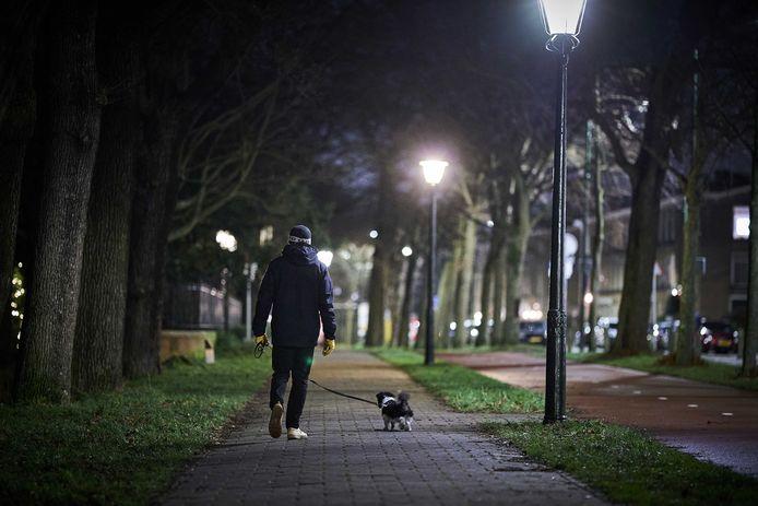 Een man laat zijn hond uit.