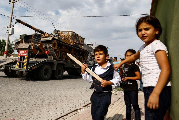 Kinderen kijken hoe Turkse tanks op transportwagens de Syrische grens oversteken, 18 oktober 2019. Beeld AP