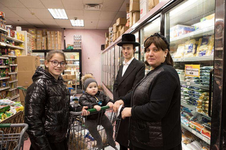 Een Joodse familie doet boodschappen in de All Fresh Supermarket in Monsey. De kinderen zijn ingeënt tegen de mazelen. Beeld chantal heijnen