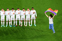 TOPSHOT - A person waving the rainbow flag runs on the pitch as the Hungary players line up for the national anthems the UEFA EURO 2020 Group F football match between Germany and Hungary at the Allianz Arena in Munich on June 23, 2021. (Photo by Matthias Hangst / POOL / AFP)
