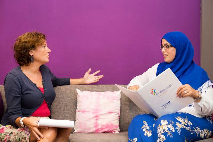 Mentor (en oud-ambtenaar) Marie-Hélène Valk (l) in gesprek met werkzoekende Amal Adlouni in buurthuis De Mussen.