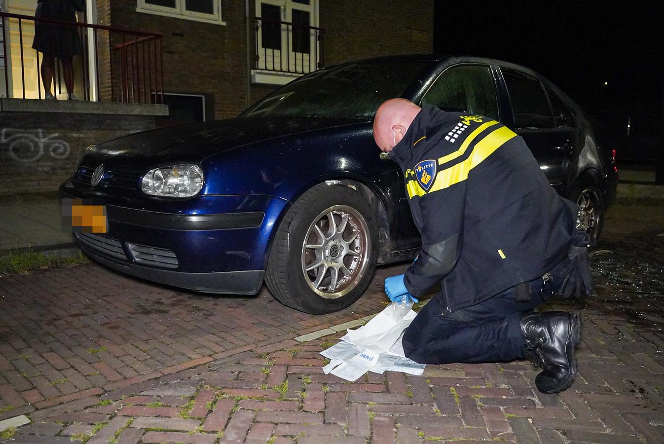 Een politieagent stelt bewijsmateriaal veilig bij de auto die tot twee keer toe op de Voetiuslaan in Arnhem in brand werd gestoken.