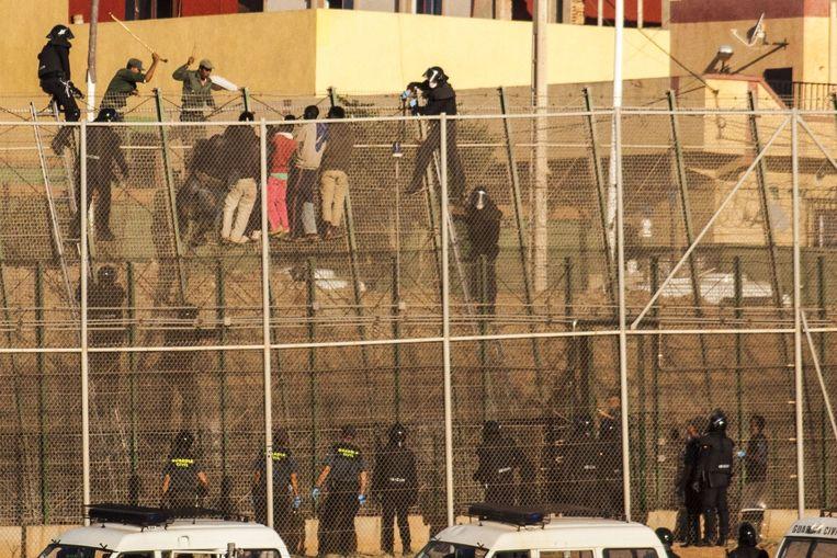 Migranten proberen de grens tussen Marokko en Spanje over te steken bij Melilla, een Spaanse exclave aan de Middellandse Zee. Beeld afp
