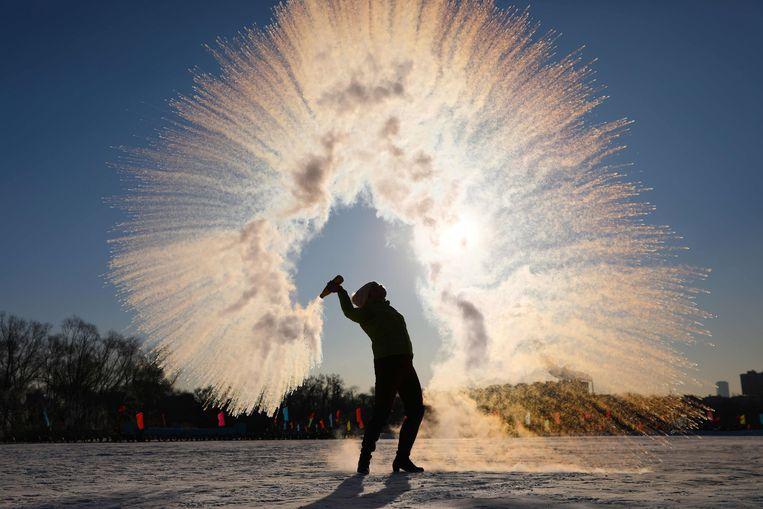 Een vrouw in Shenjang, in het noordoosten van China, gooit een fles heet water leeg, waarop het water meteen condenseert in ijskristallen. Het is er 27 graden onder nul.  Beeld AFP