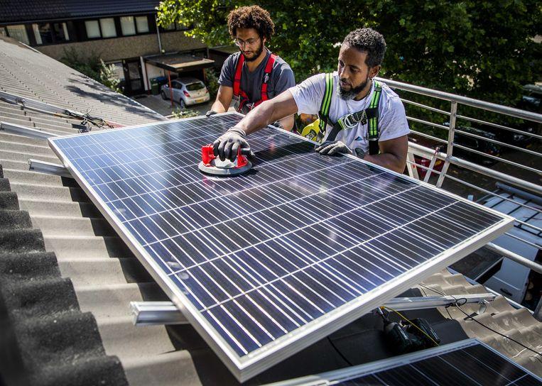 Installateurs plaatsen in Gouda zonnepanelen op het dak van een woonhuis. Beeld Remko de Waal / ANP