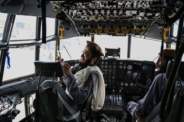 Talibanstrijders in een cockpit van een Afghaans vliegtuig op 31 augustus, de dag dat ook de laatste Amerikaanse troepen zich terugtrokken uit het land.  Beeld AFP