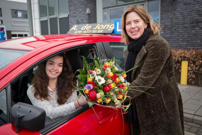 De 17-jarige Anne van Nes uit Zwijndrecht is geslaagd voor haar rijexamen en krijgt bloemen van verkeersminister Cora van Nieuwenhuizen.