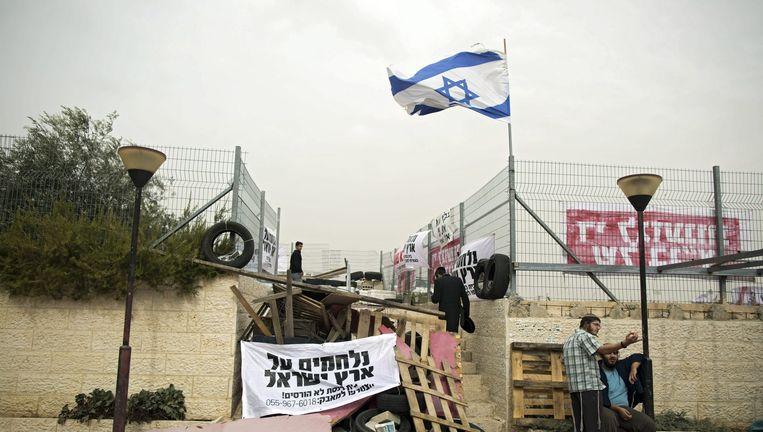 Israëlische kolonisten blokkeren de ingang van hun nederzetting. Beeld anp