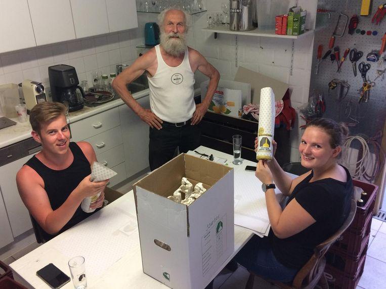 Jobstudenten Tom De Braekeleer en Ariane Verreck wikkelen Saison's voor Noorwegen in onder het toezicht oog van brouwer Jef Van Den Steen.