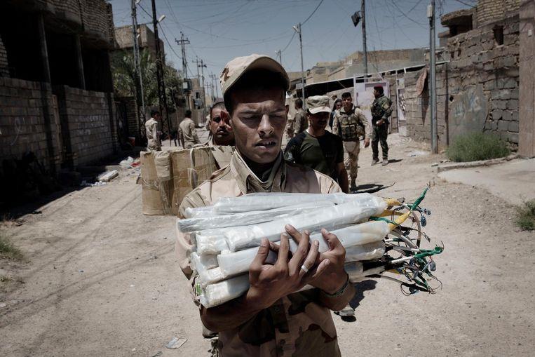 Een soldaat van de Iraakse Eerste Legerdivisie draagt door IS gefabriceerde bommen naar een vrachtwagen, die ze naar een opslagplaats moet brengen. Beeld Daniel Rosenthal / de Volkskrant