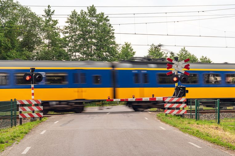 This is a photo of a railroad crossing in rural Holland. A train is moving fast by the crossing. Beeld Getty Images