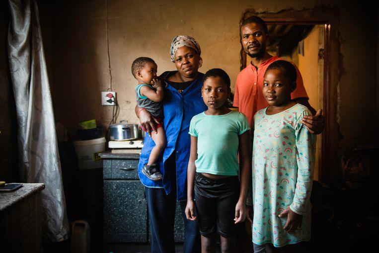 Thabang Raseboku met zijn vriendin en kinderen in hun oude townshiphuisje in Soweto.   Beeld Bram Lammers