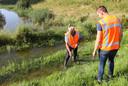 Vrijwilliger Herman Brouwers (72) uit Genderen en Ard-Jan Methorst (25) uit Veenendaal, medewerker van Waterschap Rivierenland, inspecteren het talud langs de N322 tussen Heerewaarden en Dreumel. Het Maaswater staat inmiddels tot aan het talud.