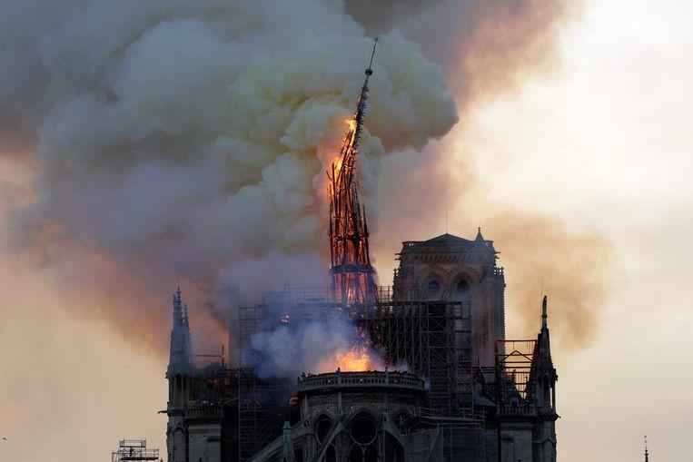 De bijna 100 meter hoge torenspits brak als een lucifer onder de vlammen. Beeld AFP