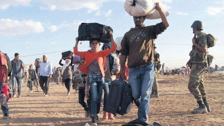 Met schaarse bezittingen steken Koerden vanuit Syrië de grens met Turkije over. Beeld reuters