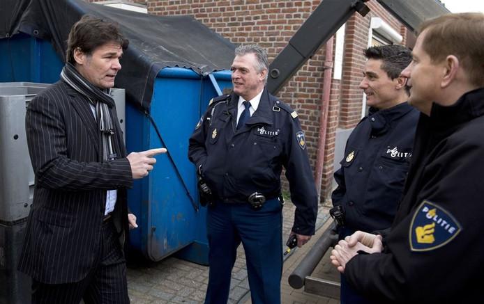 Burgemeester Paul Depla praat met politiemedewerkers die een chemisch drugslab ontruimen in een woonwijk in Hoensbroek.