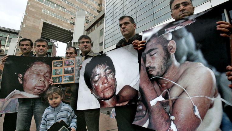 Archieffoto demonstranten met foto's van slachtoffers mosterdgas Beeld ANP