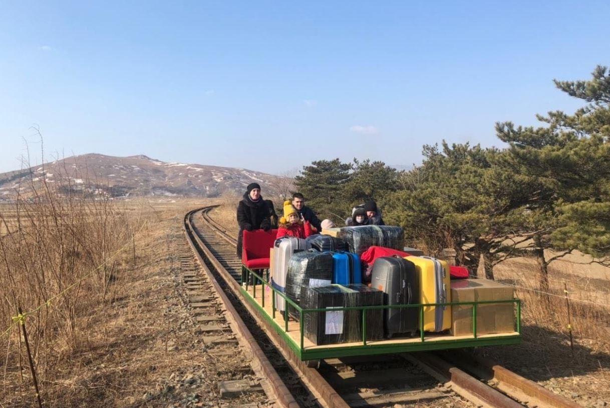 Derde secretaris Vladislav Sorokin van de Russische ambassade in Pyongyang en zijn vrouw achter de trolley met daarop hun kinderen en bagage.