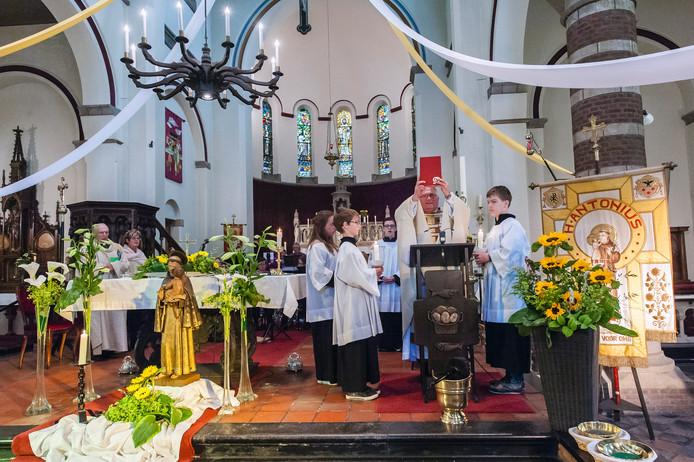 Geel houd na er uit te hebben voorgelezen het boek van het heilige sacrement omhoog