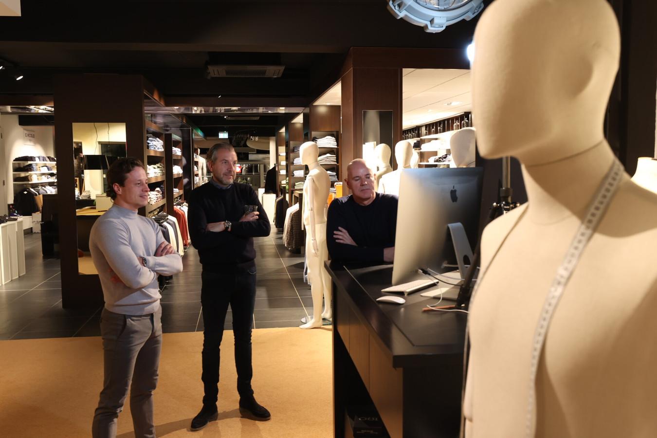Sten Burghouts, Niels Wildenberg en Jan Burghouts volgen de persconferentie in hun modezaak op de Kleine Berg in Eindhoven.