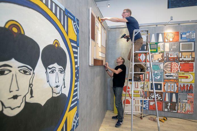 De inrichting van de expositie van kunstenaar Allard Budding in de Veenendaalse Cultuurfabriek. Op de trap de initiatiefnemer en voormalig vriend van de overleden kunstenaar, Hans Huitinck.