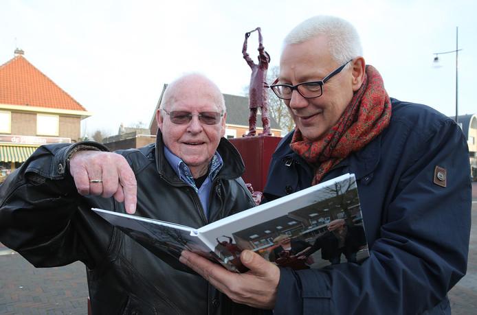 Eef van Ooijen (rechts) ontvangt als wethouder van de gemeente Brummen een boek over het ontstaan van het Papierscheppersmonument.