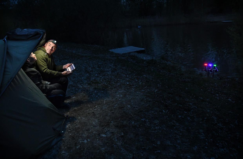Vader en zoon vissen 's nachts op karpers in visvijver 't Ber's Kuiltje.  Beeld Marcel van den Bergh / de Volkskrant