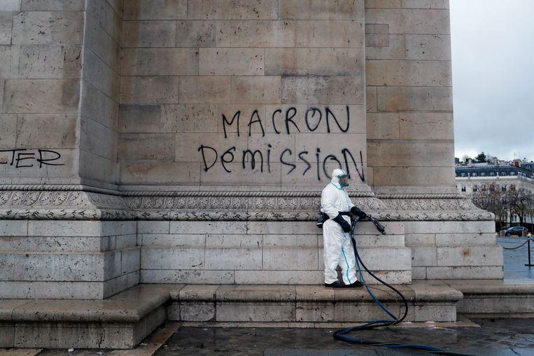"""""""Macron ontslag"""", leest de graffiti-boodschap op de Arc de Triomphe vlak voor die wordt gekuist. Beeld AP"""