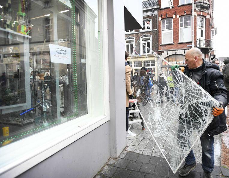 Bij een winkel in het centrum van Den Bosch wordt dinsdag de schade hersteld. Beeld ANP