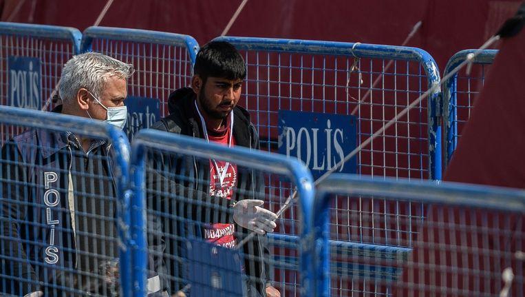 Een politieman escorteert een migrant die vanuit Griekenland terug is gebracht naar Turkije. Beeld afp