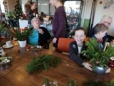 Jong en oud maken samen kerststukjes in De Meent in Groesbeek