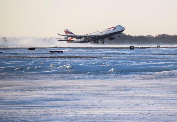 Het is een huzarenwerk om de banen van het vliegveld in Boston ijsvrij te houden. Deze vlucht van British Airways, op weg naar Londen, kon wel vertrekken.