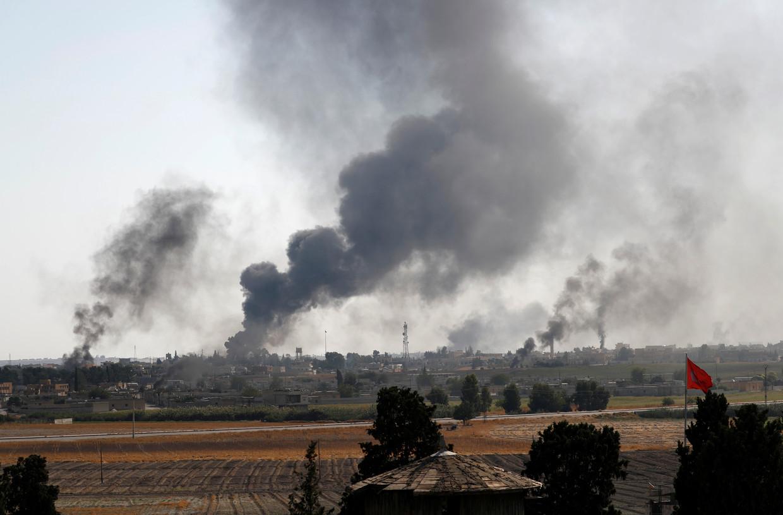 Boven de Syrische stad Tel Abyad doemen rookpluimen op.Hier vonden gisteren de felste gevechten plaats. Beeld REUTERS