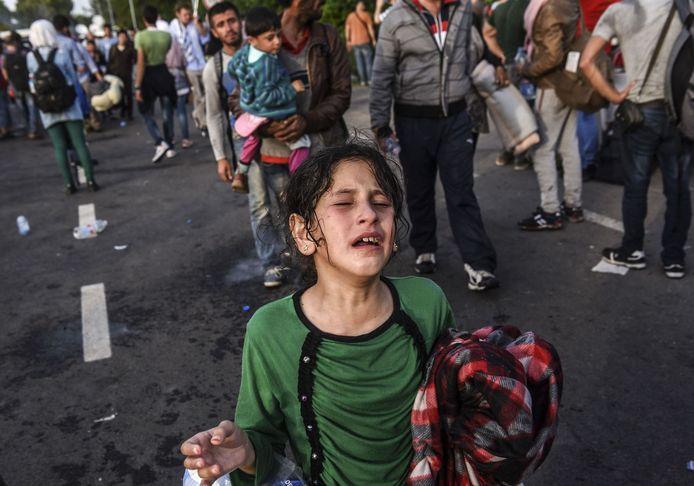 Een door traangas getroffen meisje loopt huilend over straat.